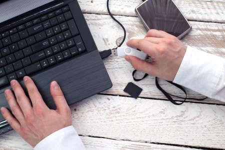 myszy: Ręka mężczyzny stawia pendrive do laptopa. Koncepcja przechowywania danych. Zdjęcie Seryjne