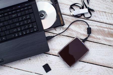 Laptop con pendrive, tarjeta SD, CD y disco duro portátil. Concepto de almacenamiento de datos. Foto de archivo - 47930353