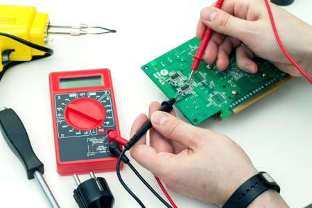 electronic hardware: Electrician checks electronic hardware with a multimeter in the workshop Stock Photo