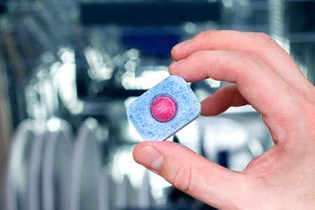lavaplatos: La mano del hombre que sostiene la tablilla lavavajillas. Lavavajillas en el fondo Foto de archivo