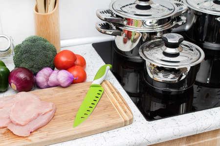 Ingredientes para un almuerzo saludable y moderna cocina de inducción con las ollas de plata. Foto de archivo