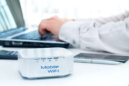 computer device: Mobile router device on the table and businessman with computer on background