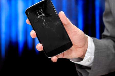 broke: Businessman shows broken smartphone with crashed screen. Stock Photo