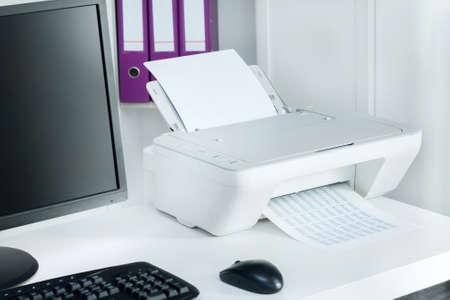 현대 사무실에서 흰색 프린터와 검은 컴퓨터의 구성