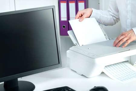 남자는 흰 종이에 종이를 집어 넣는다. 스톡 콘텐츠