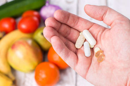 dietary supplements: Hand with dietary supplements on fruity background