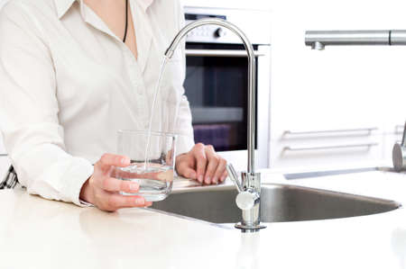 water sink: Woman pours fresh clean water into the glass Stock Photo