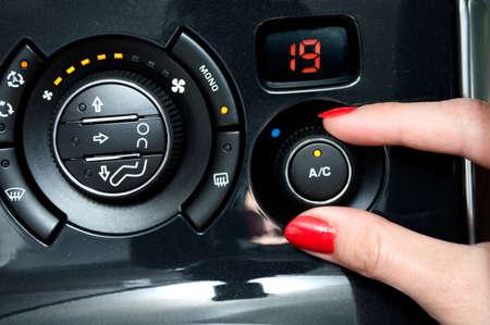 여자는 차 안에서 에어컨을 켠다. 스톡 콘텐츠