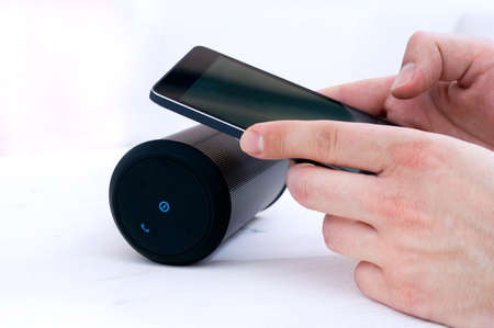 applications: Man is using his smartphone application to connect with wireless speaker. Stock Photo