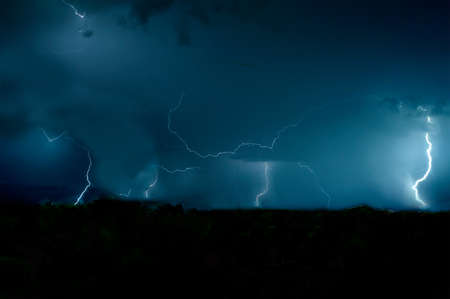 passing over: Magical storm passing over the forest at night Stock Photo
