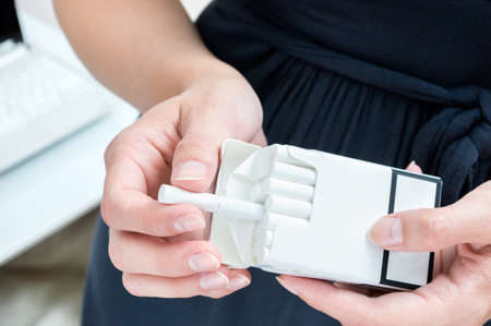 break out: Businesswoman break out a cigarette. Smoking in the workplace Stock Photo