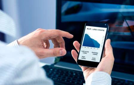 ビジネスマンは、スマート フォン アプリケーションの為替レートをチェックします。 写真素材