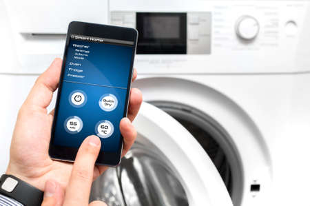 set up: Man uses his smartphone to set up the washer