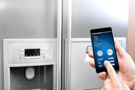 남자는 스마트 폰을 사용하여 냉장고를 설치합니다.