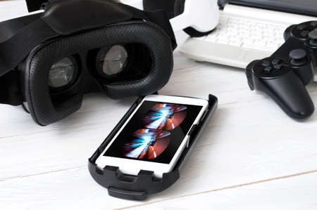 Smartphone laying on desk and prepared to play with VR googles. Game on screen was created in graphic program Stockfoto
