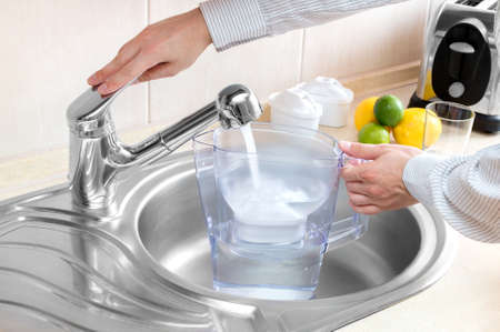 filters: Man pours water into water filter jug