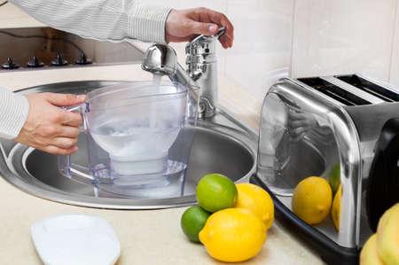 Man fills filter jug with tap water