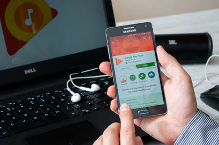 google play: WROCLAW, POLAND- SEPTEMBER 09th, 2016:  Man install Google Play Music application on Samsung A5. Google Play Music is a music streaming service and online music locker operated by Google.