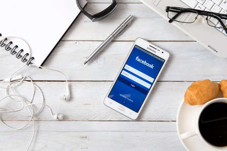 logo samsung: WROCLAW, POLAND- OCTOBER 18th, 2016 : Samsung A5 with Facebook application laying on desk. Facebook is an online social media and social networking service.