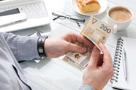 사업가 직장에서 아침 식사에서 돈을 세 고있다