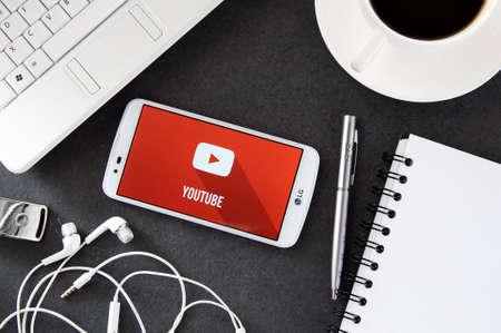 브로츠와프, 폴란드 - 2016 년 12 월 6 일 : YouTube 애플리케이션을 사용하는 LG K10이 책상 위에 놓여 있습니다. YouTube를 통해 사용자는 동영상을 업로드,보 에디토리얼