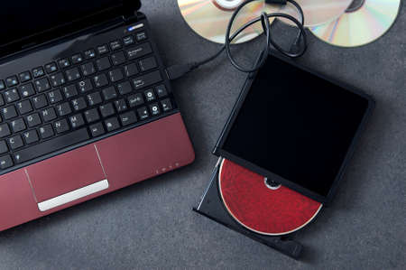 bluray: Laptop with connected portable optical drive. Conception of data storage.