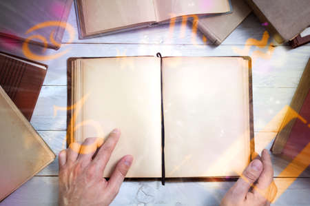 enchant: Old magic book with glowing zodiac symbols and mans hand shows important place. Empty page for your text Stock Photo