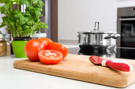 stockpot: Sliced tomatoes on wooden cutting board in modern kitchen Stock Photo