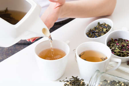 Woman poured hot green tea into cups and different kind of herbs on wooden table