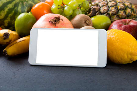 programs: White smartphone with empty screen over fruity background