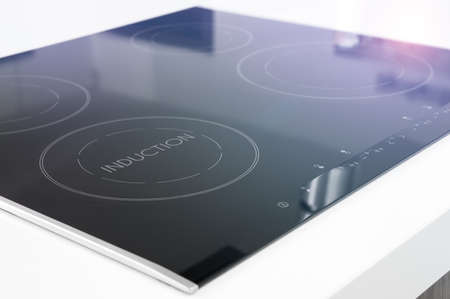 Modern black induction cooker on white countertop Stockfoto