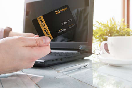 programs: Man is holding a loyalty card while office working