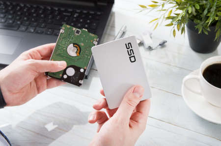 hard disk: Man changes hard drive disk to a modern ssd