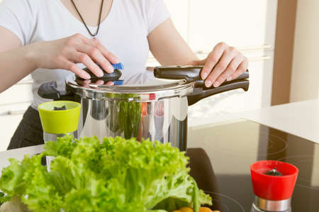 Woman uses pressure cooker to cook a meal. Conception of healthy nutrition.