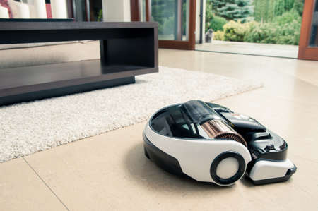 dry cleaner: Robot vacuum cleaner working in modern home