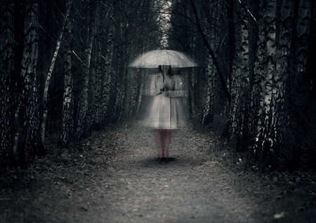 Ghost woman stands on a dark path in the forest