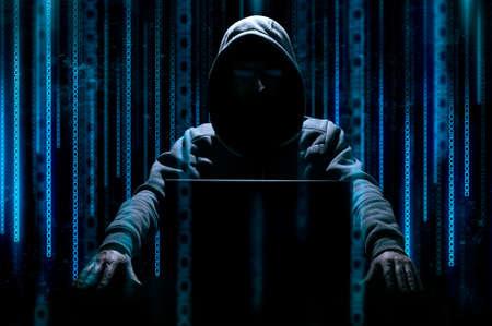 해커 배경에 이진 코드로 노트북 뒤에 앉아 스톡 콘텐츠