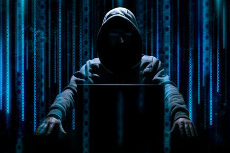 Hacker sits behind laptop with binary code on background