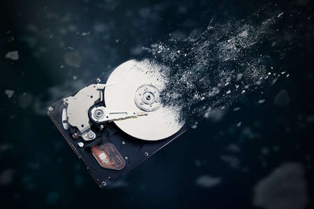 The old hard disk drive is disintegrating in space. Conception of passage of time and obsolete technology