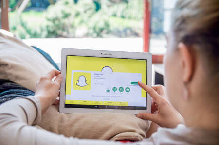 WROCLAW, POLAND- APRIL 10th, 2017:  Woman is installing Snapchat application on Lenovo tablet. Snapchat is an image messaging and multimedia mobile application