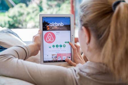 브로츠와프, 폴란드 - 2017 년 4 월 10 일 : 여성이 Airbnb 응용 프로그램을 Lenovo 태블릿에 설치하고 있습니다. 에어 비앤비 (Airbnb)는 온라인 마켓 플레이스