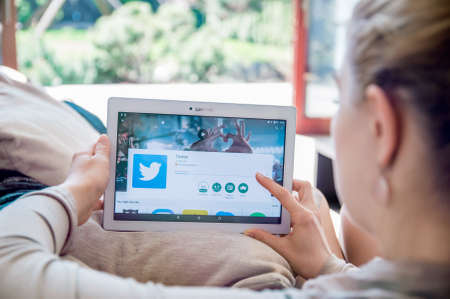 브로츠와프, 폴란드 - 2017 년 4 월 10 일 : 여자가 레노버 타블렛에 트위터 응용 프로그램을 설치하고 있습니다. Twitter는 사용자가 메시지를 게시하고 메
