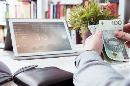 finance manager: Man holds money. Personal finance manager application in background Stock Photo