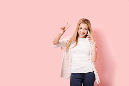 triumphing: Beautiful young girl is triumphing while talking by her smartphone and shows victory sign