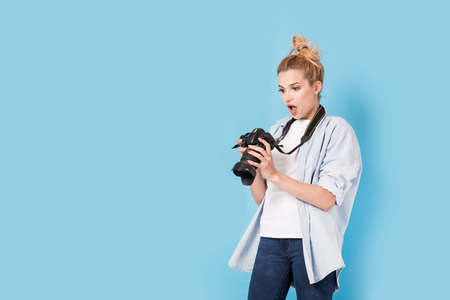 Young blonde photographer is shocked about photo she made. Model isolated on a blue background with copy space