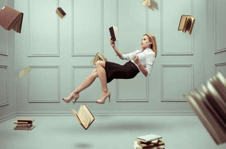 A relaxed woman levitates in a room full of flying books 版權商用圖片 - 84982209