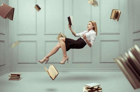 Una mujer relajada levita en una habitación llena de libros voladores Foto de archivo - 84982209