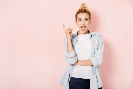 Young blonde girl with an idea on pink background