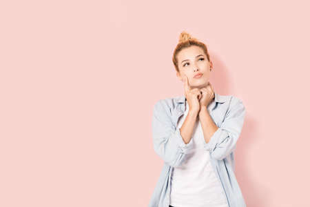 invents: Young blonde girl with a wondering look on pink background Stock Photo
