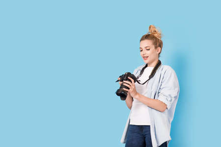 Woman photographer is satisfied about her work. Model isolated on a blue background with copy space Stock Photo